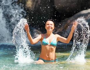Young woman relaxing in waterfall