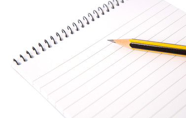 Notepad and pencil over white background