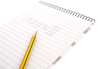 Concept image of the word vacation on a notepad with pencil