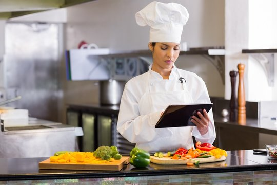 Female chef using digital tablet while cutting vegetables