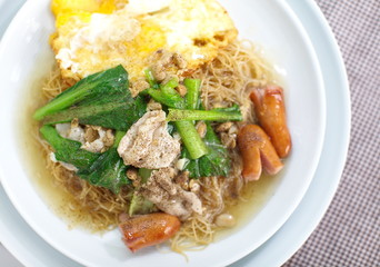 Chinese style deep fried yellow noodles with pork and fried egg