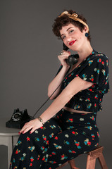 Pinup Girl in Flowered Outfit Smiles Gently on the Phone