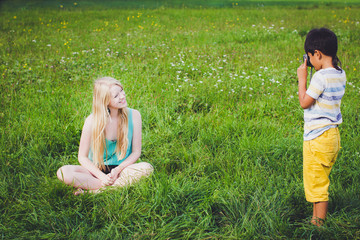 Boy and girl taking pictures in green meadow