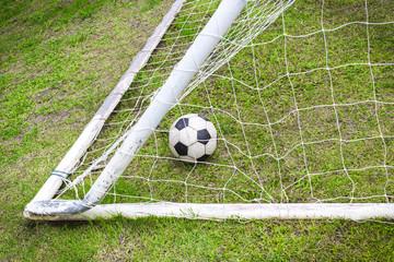 Old soccer ball in old goal net