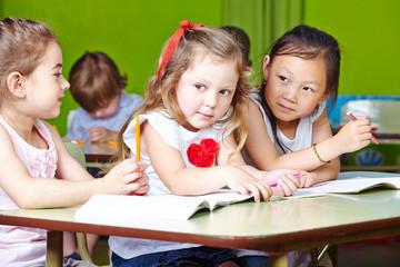 Drei Mädchen malen im Kindergarten