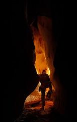 Fototapeten Braun Underground cave passage with a caver