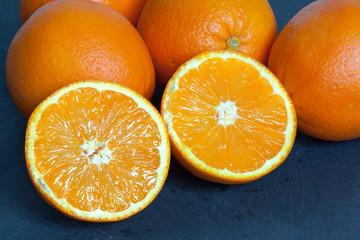 Orange coupée en deux sur fond d'ardoise