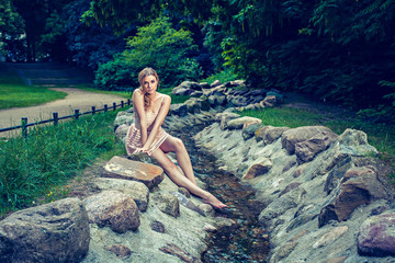 Gorgeous woman sitting on rock by stream in park