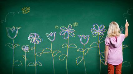 kleines Kind malt Blumen mit Kreide