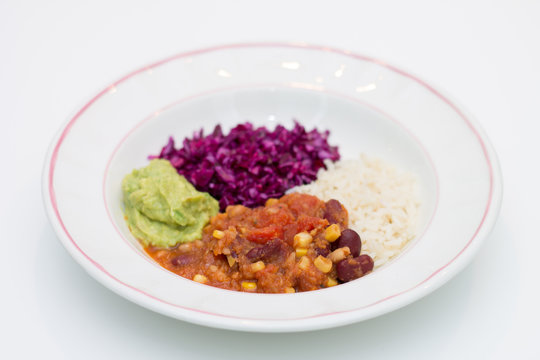 White plate of chili sin carne with red cabbage, guacamole and r