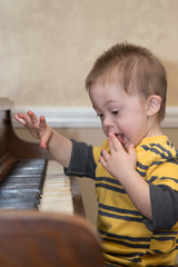 Young Down Syndrome child playing on piano