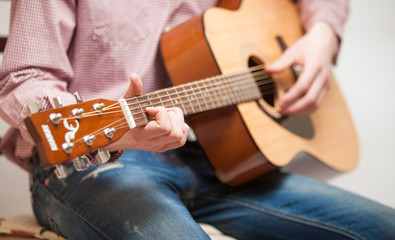 Closeup shot of man in jeans sitting and playing guitar