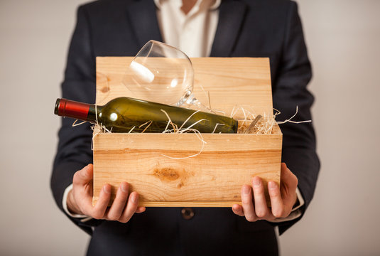 portrait of man in jacket holding open box with bottle of wine