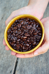Coffee beans in  bowl on hands