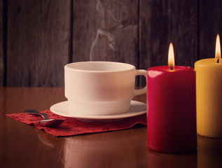 cup of coffee and candles  on wooden background