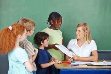 Lehrerin gibt Klassenarbeit an Schüler