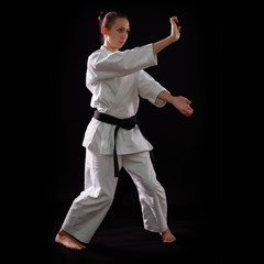 karate girl with black belt posing, champion of the world, on bl