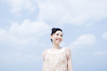 smiling woman standing under blue sky