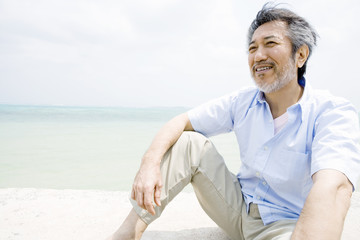 man sitting on beach looks at view