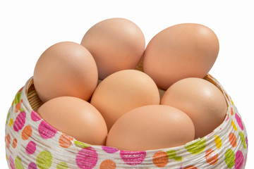 Brown eggs in a basket isolated on white background
