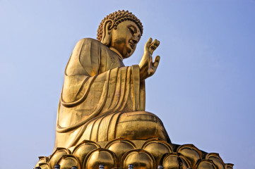 golden buddha statue with blue sky background