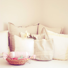 Knitting needles in basket and cute tote bag on the bed with ret