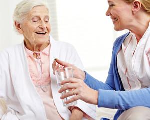 Wall Mural - Seniorin nimmt Tablette mit Wasser