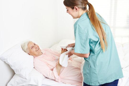 Krankenschwester wäscht eine bettlägerige Seniorin