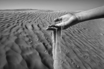 Womans hand in the sand black and white