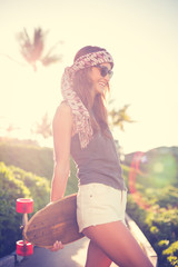 Hipster girl with skate board wearing sunglasses
