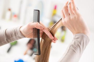Hairdresser cut hair of a woman.