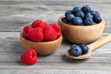 Blueberry and raspberries in bowls on wooden background