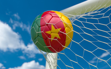 Cameroon flag and soccer ball in goal net