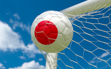 Japan flag and soccer ball in goal net