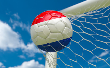 Netherlands flag and soccer ball in goal net