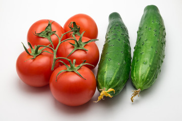 Five tomatoes and two cucumber on a white background