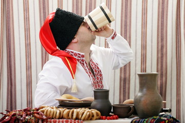 Ukrainian Cossack is sitting at the table and eats