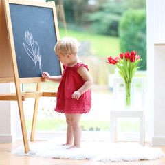 Cute toddler girl drawing tulips with chalk on black board