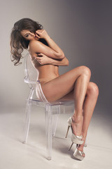 Sensual brunette woman with long curly hair sitting on chair