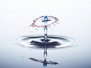 Blue water drop hits red umbrella