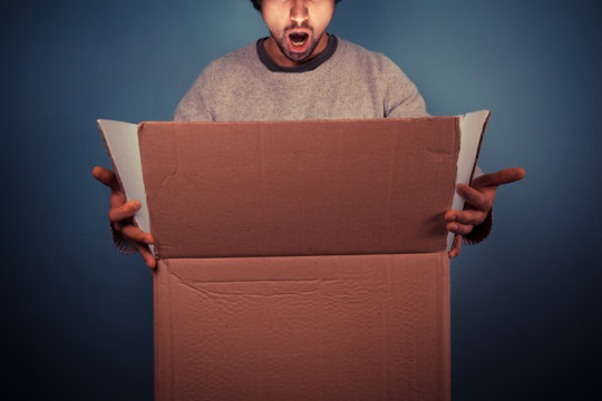 Surprised young man opening exciting box