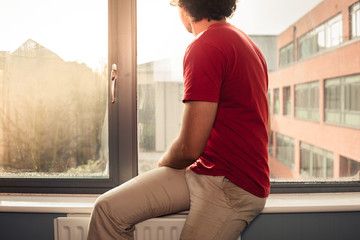 Young man on window sill