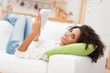 entspannte frau liest auf dem sofa