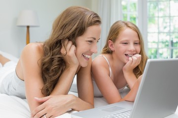 Happy mother and daughter using laptop in bed