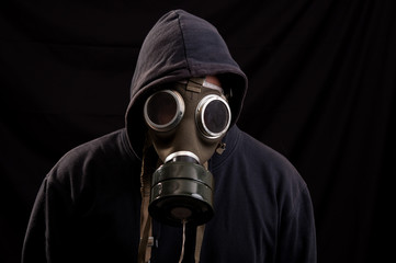 Man in black clothes wearing a classic gas mask over a dark back