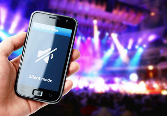 Hand holding smartphone with mute sound during concert