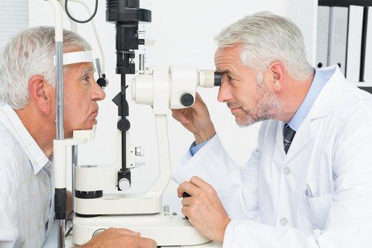Optometrist doing sight testing for senior patient