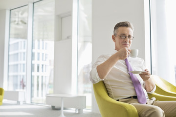 Mature businessman having coffee at office lobby