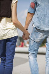 Mid section rear view of couple holding hands outdoors