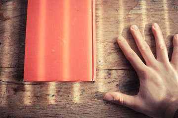 Hand and book on table
